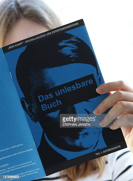A woman poses with an extra booklet with excerpts from German dictator Adolf Hitler's book Mein Kampf from the Zeitungszeugen newspaper on January 25...