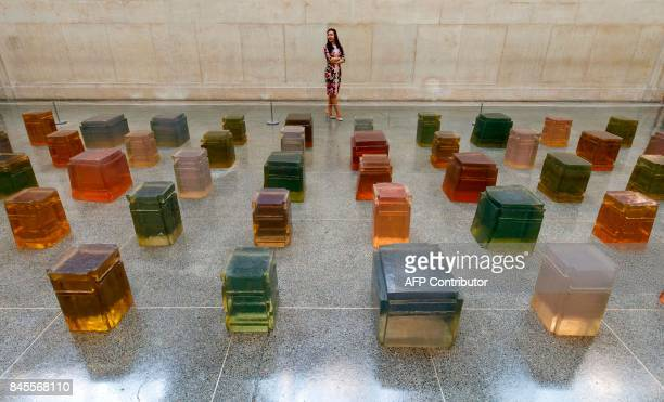 A woman poses with an installation entitled 'Untitled 1995' an installation of 100 jewellike resin casts of the underside of chairs by British artist...