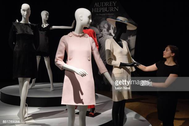 A woman poses with an ivory wool Jersey dress during a preview of items from the sale of actrees Audrey Hepburn's personal collection at Christies on...