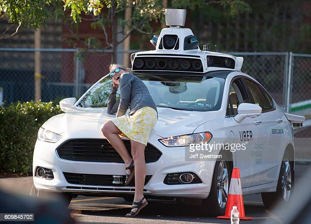 A woman poses with an Uber driverless Ford Fusion as it sits in the Uber Technical Center parking lot on September 2016 in Pittsburgh Pennsylvania...