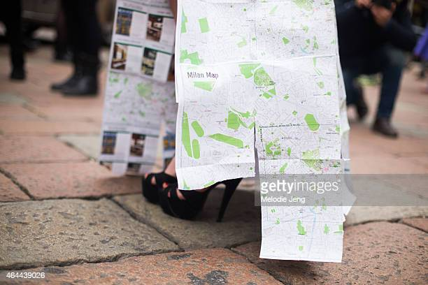A woman poses with dress made from Milan's map outside the Gucci show at Piazaa Oberdan on February 25 2015 in Milan Italy