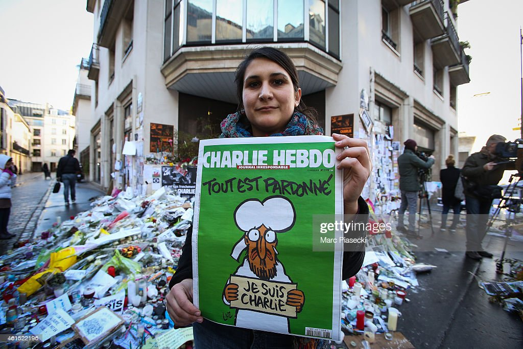 A woman poses with her copy of the French satirical magazine 'Charlie Hebdo' in front of the 'Rue Nicolas Appert' on January 14, 2015 in Paris, France. An initial three million copies of the controversial magazine were printed in the wake of last week's terrorist attacks. Another two million of the magazine is scheduled for printing.