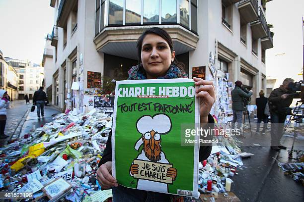 Woman poses with her copy of the French satirical magazine 'Charlie Hebdo' in front of the 'Rue Nicolas Appert' on January 14, 2015 in Paris, France....