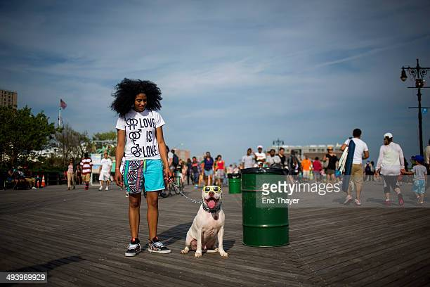 A woman poses with her dog at Coney Island on Memorial Day May 26 2014 in the Brooklyn borough of New York City Memorial Day originally celebrated as...