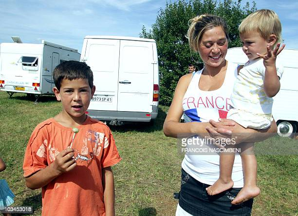 A woman poses with kids in front of caravans on August 19 2010 on an airfield where people belonging to the Roma community camp in SemoutiersMontsaon...
