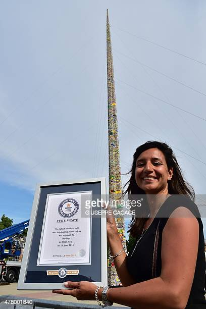 A woman poses with the Guinness World Record certificate in front of a 3550 meters high tower of Lego plastic bricks at the 'Fabbrica del Vapore' in...