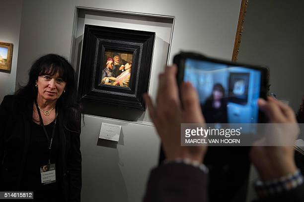 A woman poses with the painting 'The Unconscious Patient' by Rembrandt van Rijn during the press preview of The European Fine Art Fair in Maastricht...