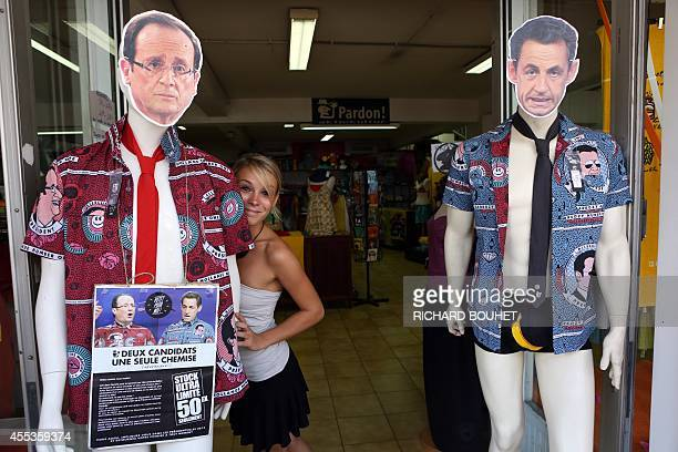 A woman poses with two dummies wearing shirts representing France's incumbent President and rightwing ruling party Union for a Popular Movement...