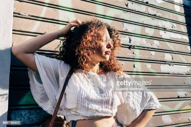 Woman posing against roller shutters