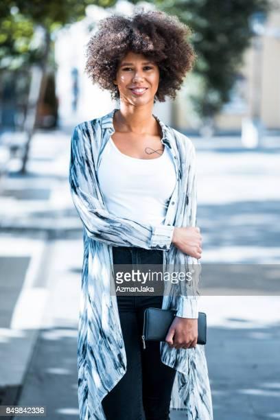 Frau posiert lächelnd in der Stadt
