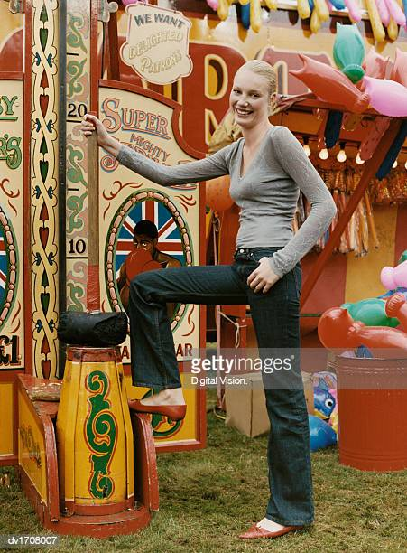 Woman Posing at an Old Fashioned Fairground Strength Game, Holding a Large Mallet
