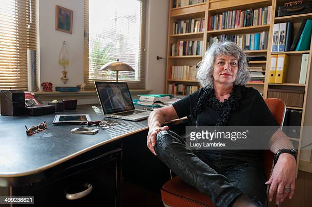 Woman posing by her desk at home office