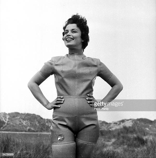 A woman posing in a cutoff wetsuit before taking a dip in the sea