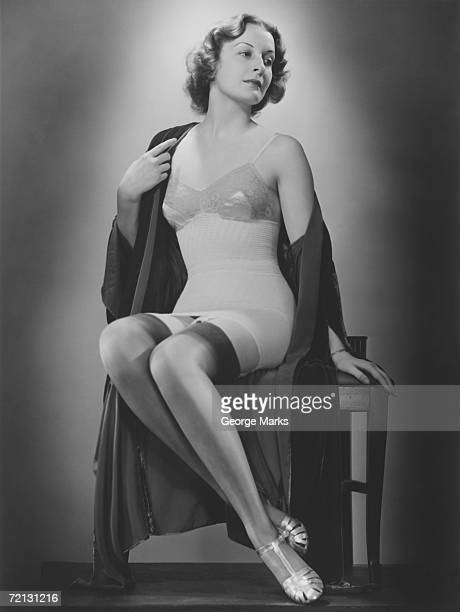 Woman posing in corset and stockings (B&W), portrait