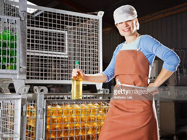 woman posing in front of bins of bottles - industrial storage bins stock pictures, royalty-free photos & images