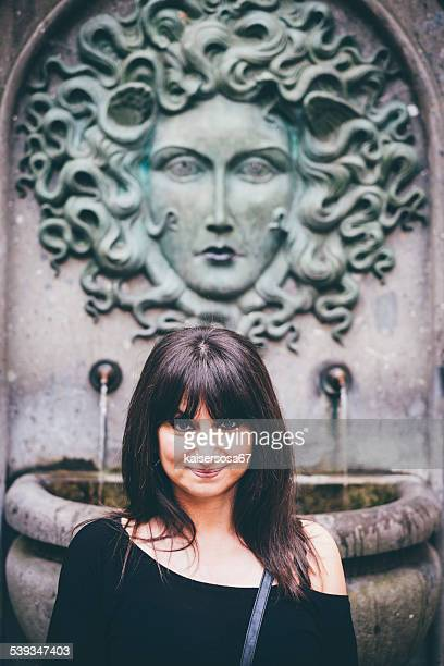woman posing in front of medusa fountain - medusa stock photos and pictures