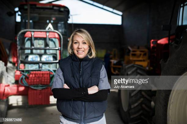 kvinna poserar på landsbygden traktorer lager. kvinna poserar på landsbygden traktorer lager. leende tittar på kameran - mid adult women bildbanksfoton och bilder