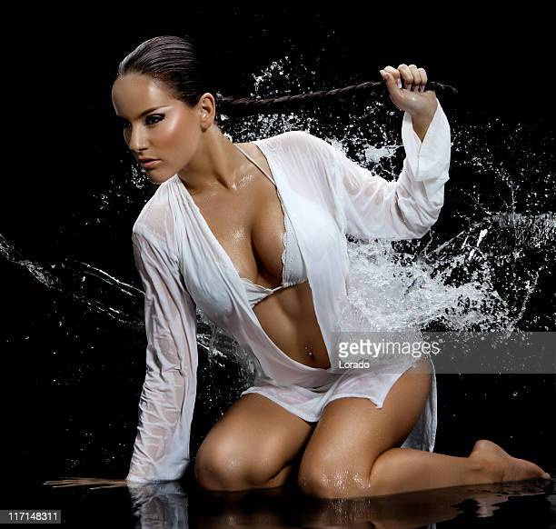 woman posing in splashing water - women in see through tops stock photos and pictures
