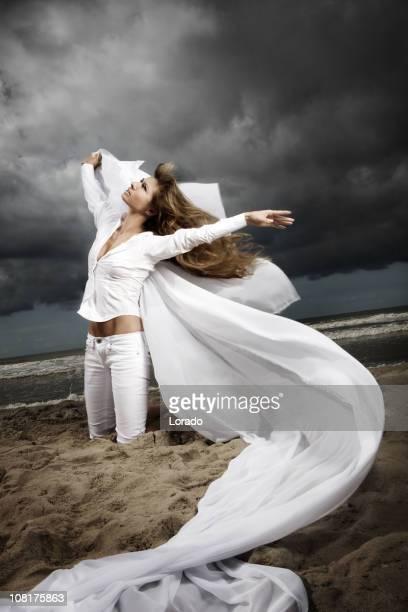 ビーチでポーズを取る女性に不安定な空模様