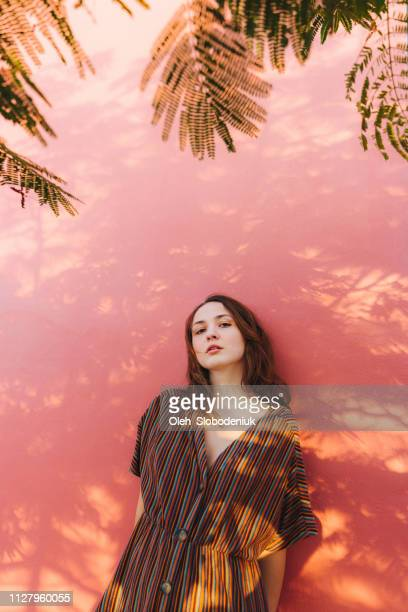 woman posing on the background of pink wall - jordan model stock pictures, royalty-free photos & images