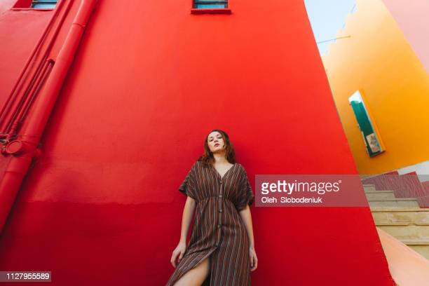 woman posing on the background of red wall - jordan model stock pictures, royalty-free photos & images