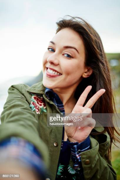 woman posing while taking selfie against clear sky - self portrait stock pictures, royalty-free photos & images