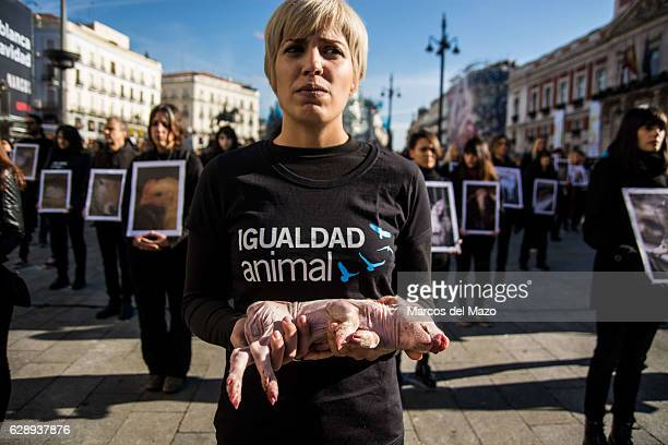 A woman posing with a dead pig during the International Animal Rights Day