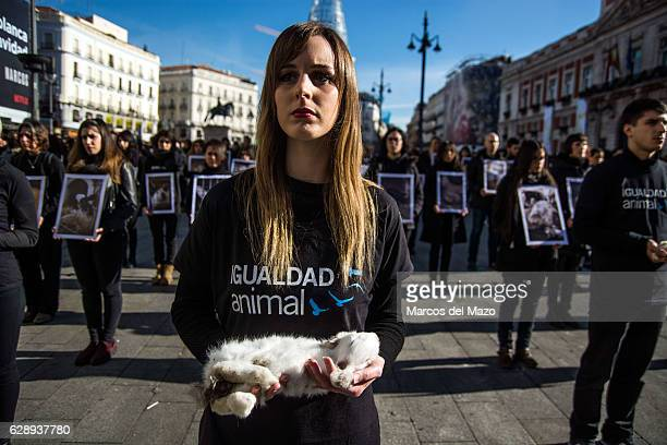 A woman posing with a dead rabbit during the International Animal Rights Day
