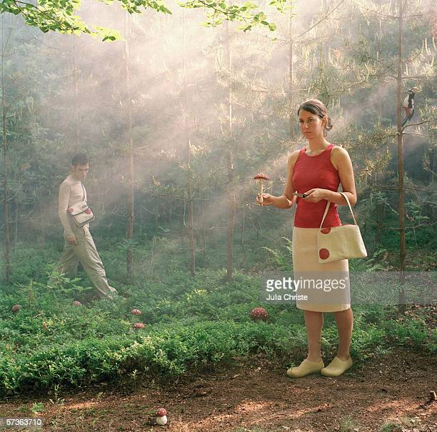 a woman posing with a mushroom and a knife in a forest - poisonous mushroom stock photos and pictures