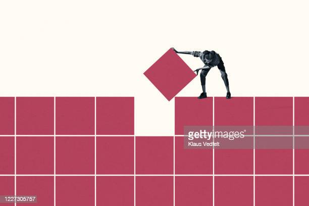 woman positioning final magenta block in grid - solutions stock pictures, royalty-free photos & images