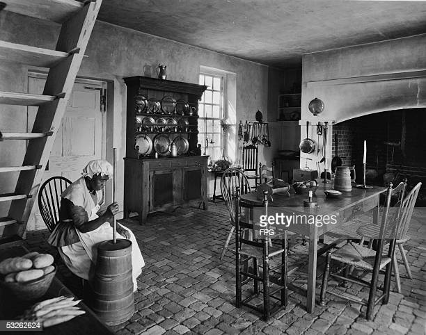 A woman possibly in the the role of slave wears period costume as shesits and churns butter in a replica of a large colonial era kitchen mid 20th...
