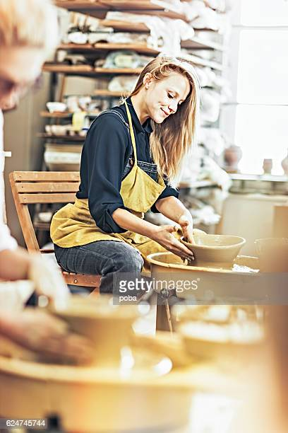 woman potter  in workshop working on pottery wheel