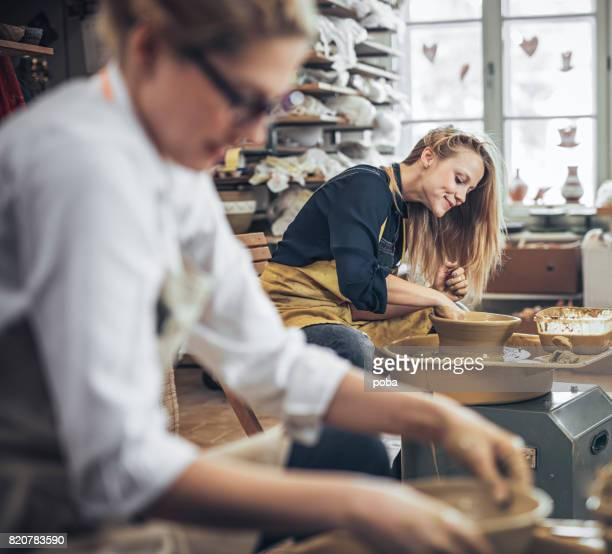 woman potter in workshop working on pottery wheel - craft product stock photos and pictures