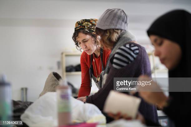 Woman pottery artist instructing student during workshop