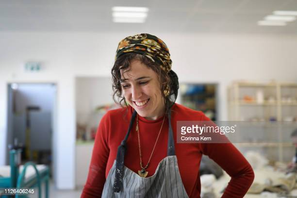 woman pottery artist laughing in studio - israeli woman stock pictures, royalty-free photos & images