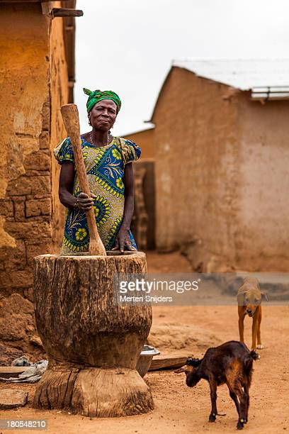 Woman pounding food on a village square