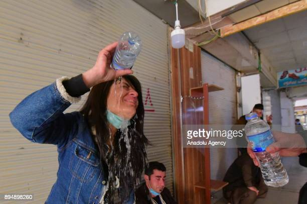 A woman poures water on her face as she is effected from the tear gas smoke while demonstrators clash with riot police within antigovernment protests...