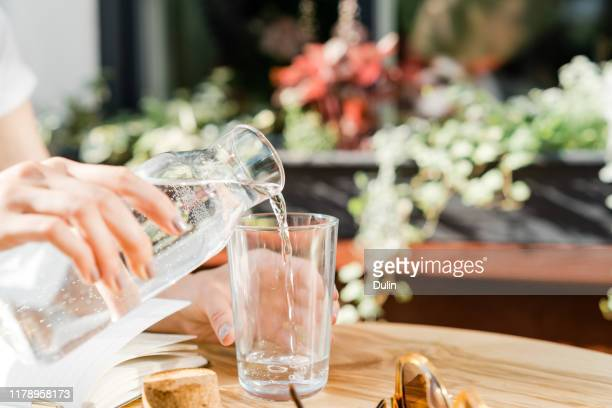 woman pouring a glass of water - copo imagens e fotografias de stock