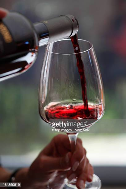 A woman pouring a sampling of red wine at a wine tasting, focus on hands