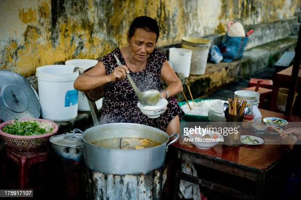 CONTENT] A woman pouring a soup in a small street restaurant in Hoi An As one of Unesco Heritage Sites a little and peaceful ancient town of Hoi An...