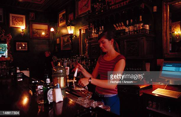 Woman pouring beer in bar.