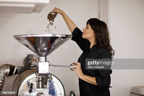Woman pouring cocoa beans into funnel