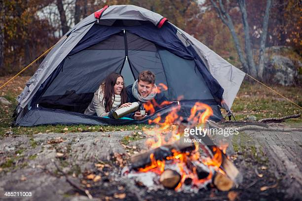 Woman pouring coffee for man while lying in tent at forest