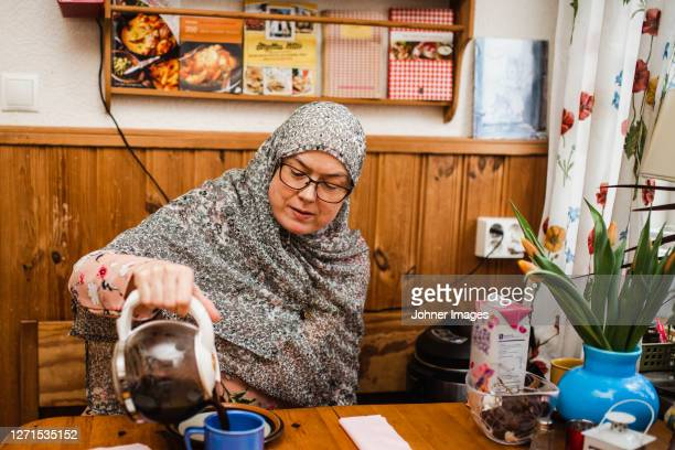 woman pouring coffee in cup - västra götaland county stock pictures, royalty-free photos & images