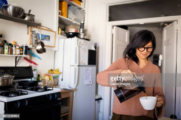 Woman pouring coffee in cup while standing in kitchen