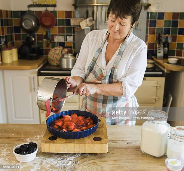 A woman pouring cooked apple and blackberry fruits in to a pie dish.