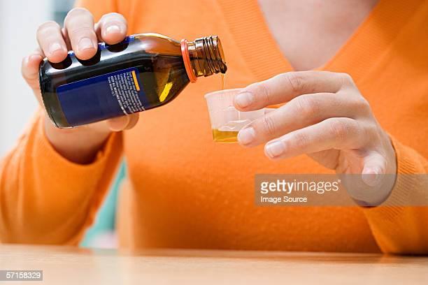 Woman pouring cough medicine
