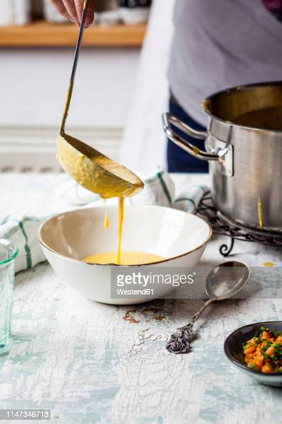 woman pouring creme of carrot soup into a bowl, partial view - soup bowl stock pictures, royalty-free photos & images
