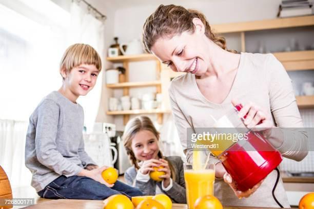 woman pouring freshly squeezed orange juice into glass for children - hausfrau stock-fotos und bilder