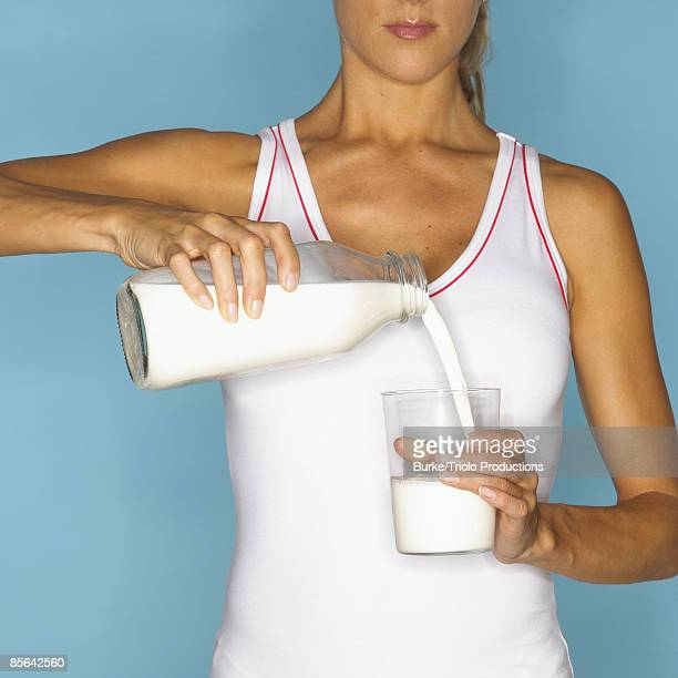 Woman Pouring Glass of Milk